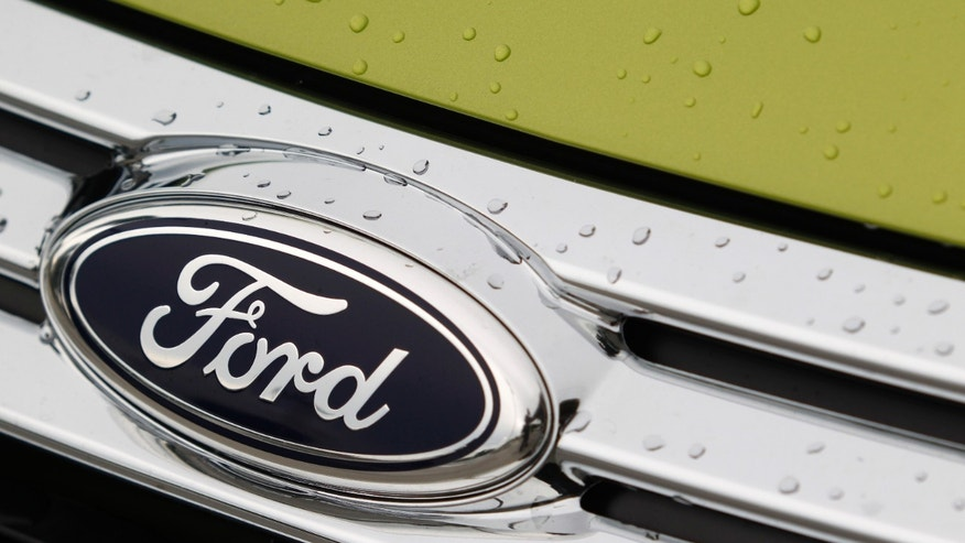 This Aug. 31, 2011 photo, shows raindrops on the grill of a Lime Squeeze Metallic 2012 Ford Fiesta SE at the Maroone Ford of Miami dealership. Ford Motor Co. and the United Auto Workers have come to terms on a new four-year contract Tuesday, Oct. 4, 2011, that trades annual pay raises for profit sharing and a signing bonus and promises thousands of new jobs building cars and trucks. (AP Photo/Wilfredo Lee)