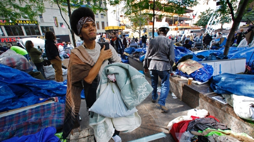 """Oct. 5: Christian Blackfeather Ruiz, 19, from Bronx, New York, searches for a spot to camp among participants in the Occupy Wall Street Protest at Zuccotti Park in lower Manhattan. """"I am here for a global economy,"""" said Ruiz."""