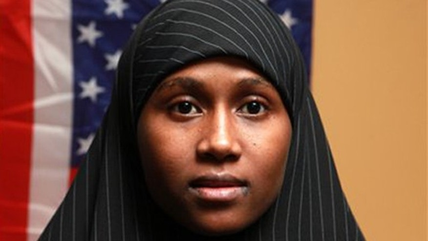 In this Thursday, Oct. 6, 2011 photo, Zainab Aweis, 20, a Somali Muslim poses in front of an American flag in Seattle, Wash.