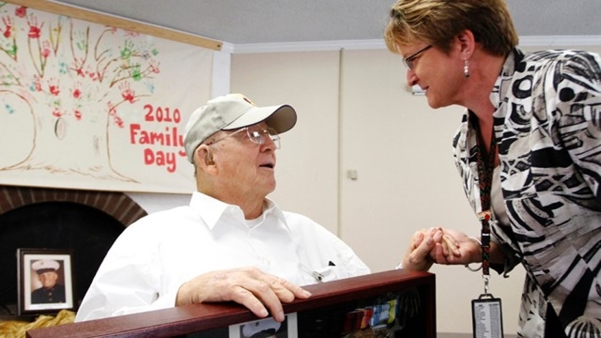 Oct. 11, 2011: Ann Narciso, chief nurse for extended care at the VA Palo Alto Health Care System, congratulates retired U.S. Marine Corps Sgt. Eugene Bradford during his Purple Heart award ceremony at the VA Menlo Park Community Living Center.