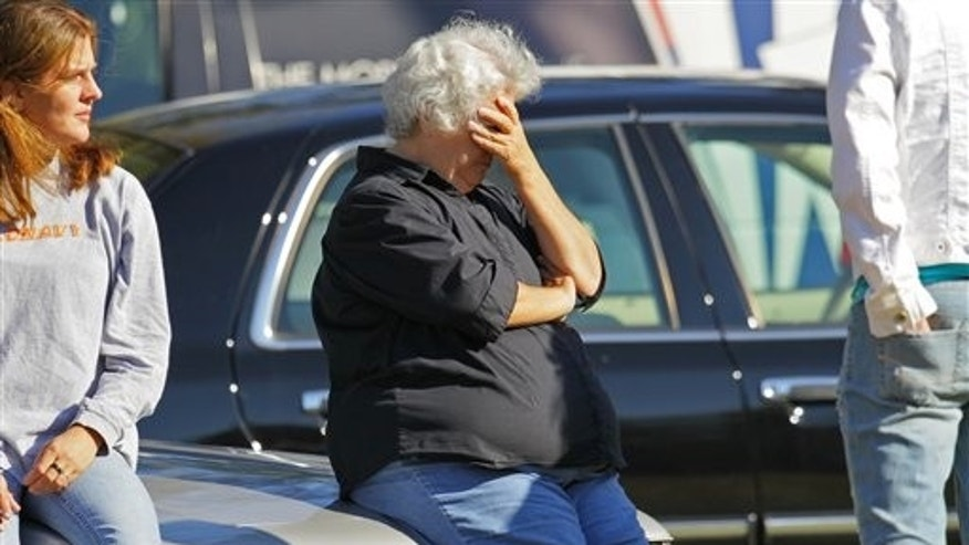 October 14: Susan Gilstrap holds her head outside the crime scene in Liberty, S.C.
