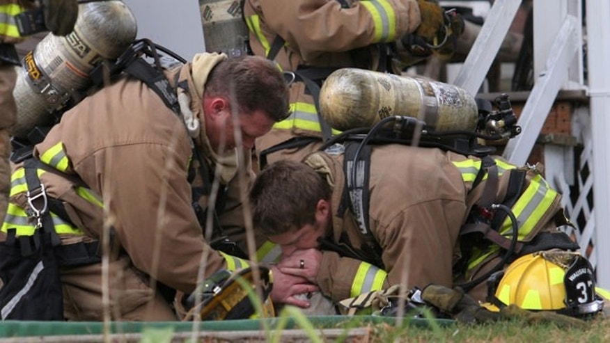 Oct. 18. 2011: Wausau firefighters Jared Thompson, left, and Jamie Giese give artificial respiration to a dog that was rescued from a house fire in Wausau, Wis.. The dog, a 7-year-old yellow lab named Coda, was reported to be in good condition following the incident.