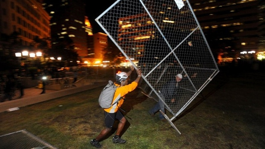 Oct. 26, 2011: An Occupy Oakland protester topples a fence outside city hall in Oakland, Calif. The fence was meant to keep out protesters who had camped out for the past two weeks before police raided the plaza early Tuesday.