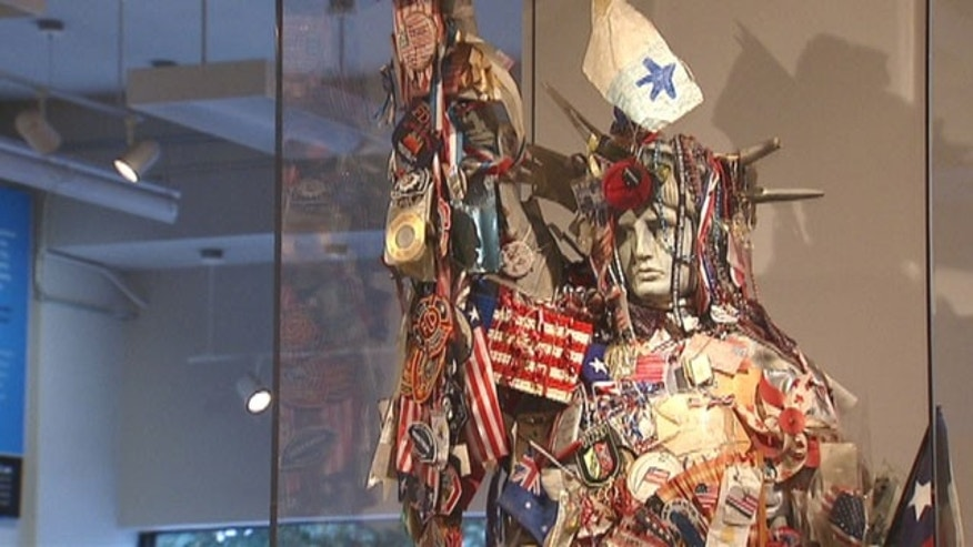 A 9-foot tall replica of the Statue of Liberty is draped in colorful flags, photographs, notes, and tributes at the National 9/11 Memorial Museum in New York City.