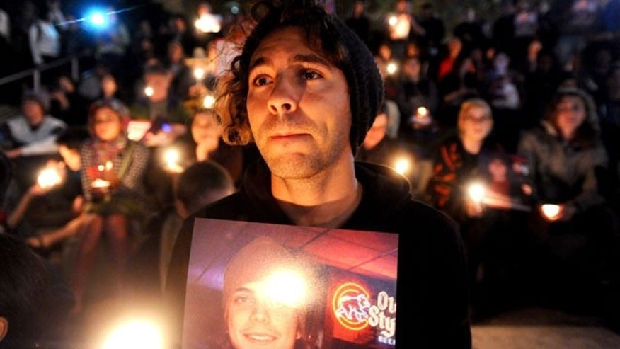 Oct. 27, 2011: Zachary Greer holds a photo of Scott Olsen during a candlelight vigil.