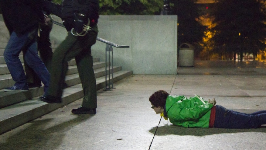 Oct. 28, 2011: An arrested woman watches from the ground of the Legislative Plaza in Nashville, Tenn.