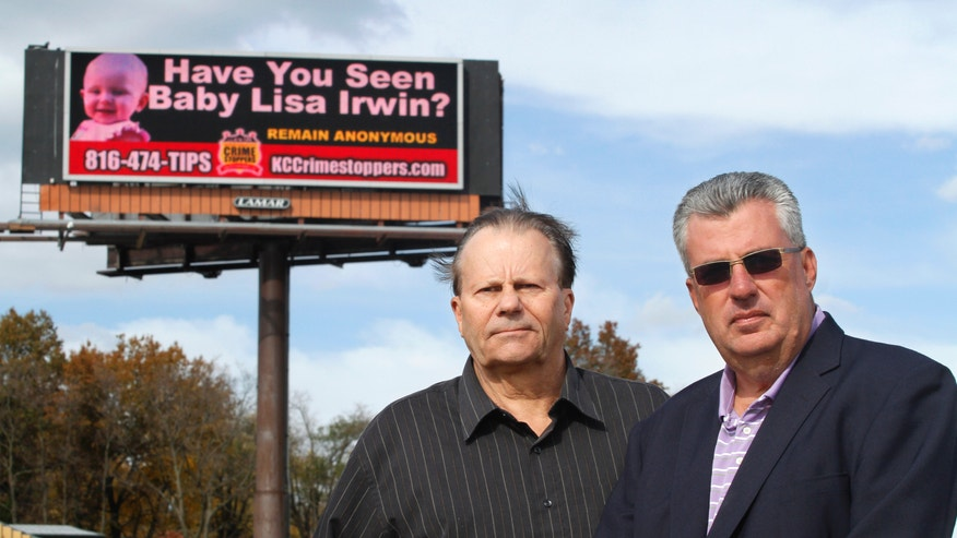 Oct. 27, 2011: Roger Kemp, left, and Bob Fessler, vice president and general manager of Lamar, pose near an electronic billboard with an alert for baby Lisa Irwin, in Kansas City, Mo.