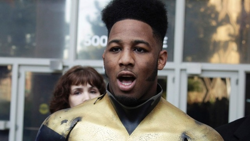 "In this Oct. 13, 2011 file photo, Benjamin Fodor, a self-styled superhero who goes by the name ""Phoenix Jones,"" talks to reporters after Fodor appeared in court in Seattle."