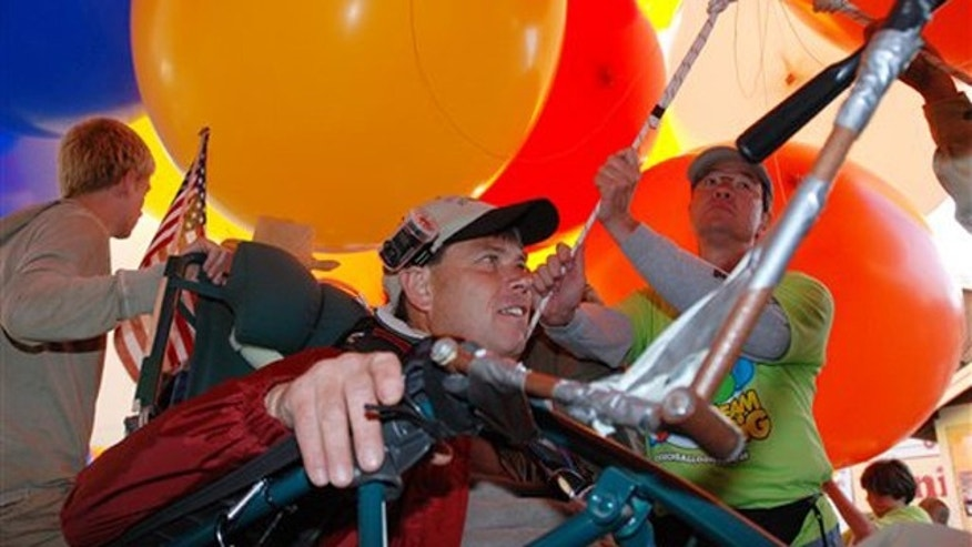 This July 5, 2008 file photo shows Kent Couch just before flying away from his gas station in Bend, Ore., riding a lawn chair rigged with more than 150 giant party balloons for a flight that ended in an Idaho farm field. Couch headed Thursday for Dubai, where he is preparing for a Nov. 15 launch in Baghdad of a double lawn chair with 300 baloons to inspire Iraqi youth.