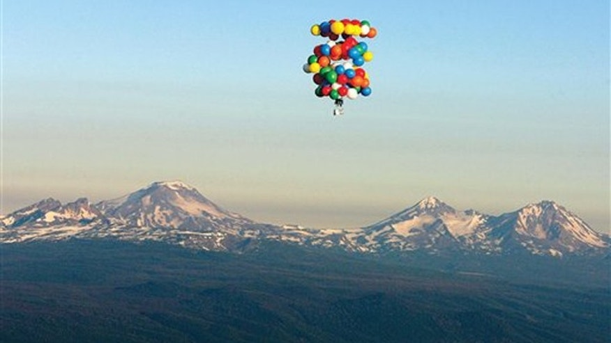 In this July 7, 2007 file photo, cluster balloonist Kent Couch, sitting in a lawn chair, ascends near Bend, Ore., past Mount Bachelor to his cruising altitude at the start of his attempt to fly to Idaho.