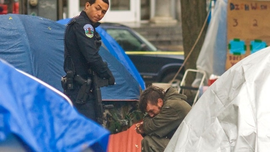 Nov. 10, 2011: A Burlington, Vt., police officer questions a witness at the Occupy Burlington encampment in City Hall Park after a man suffered a gun shot wound.
