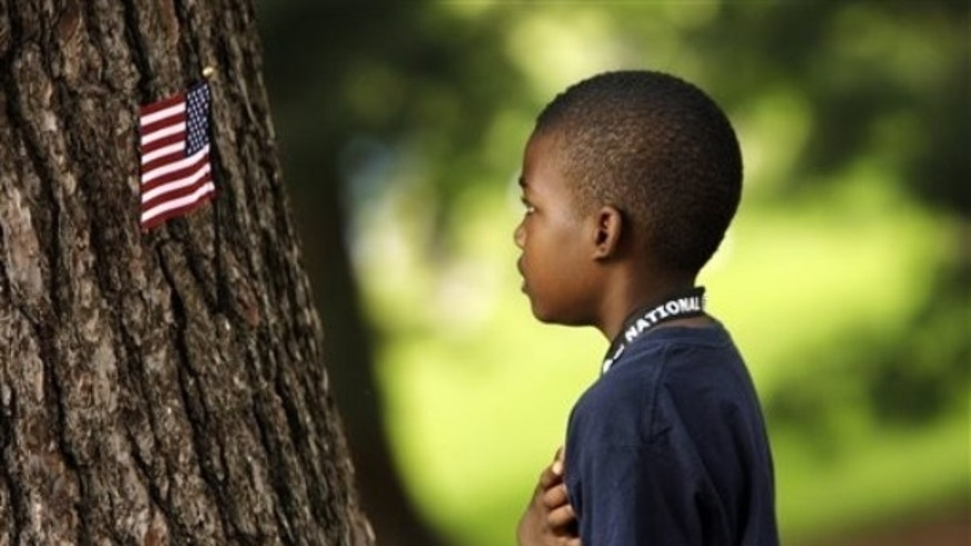 A child says the Pledge of Allegiance after placing an American flag on a tree during the second round of the AT&amp&#x3b;T National golf tournament at Congressional Country Club, Friday, July 3, 2009, in Bethesda, Md. (AP Photo/Haraz N. Ghanbari)