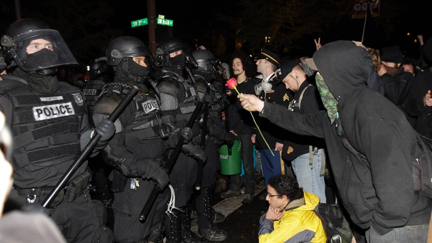 Nov. 13, 2011: A protester offers police a rose after the deadline passed when the city wanted them to vacate the Occupy Portland Camp in Portland, Ore.  Thousands of protesters showed up as mounted police and police in riot gear moved in but were forced to back down by the crowd.