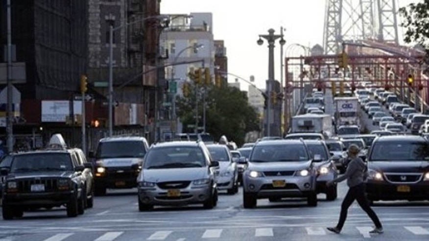 May 29, 2011: A pedestrian crosses Delancey Street ahead of morning rush hour traffic making it's way into Manhattan over the Williamsburg Bridge in New York.