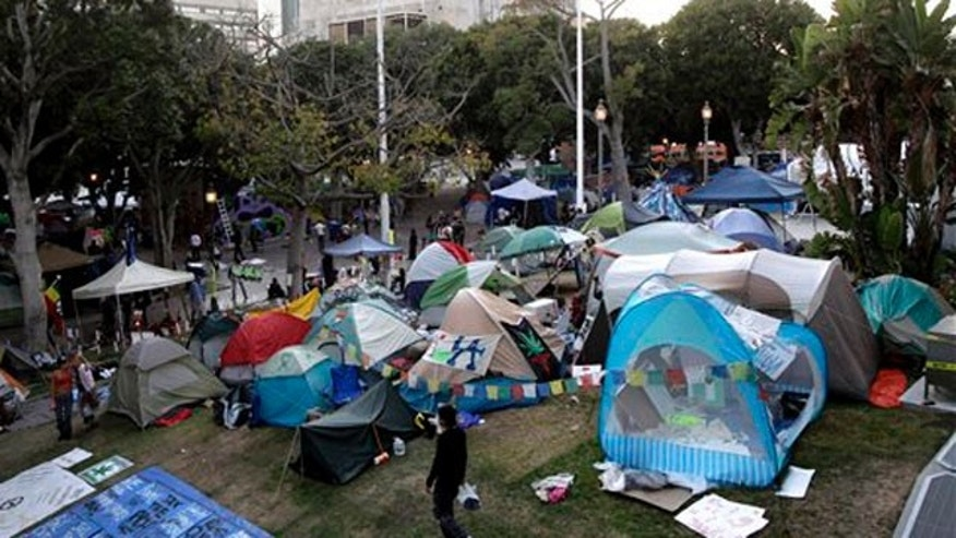 In this Nov. 2, 2011 photo, an Occupy Los Angeles protester walks past tents set up outside Los Angeles City Hall in Los Angeles.