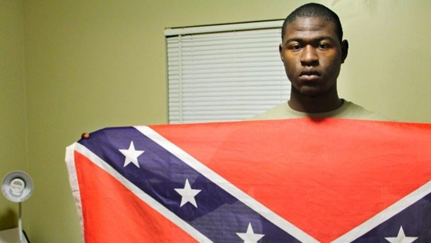 Byron Thomas, 19, a student at USCB holds a Confederate battle flag in his dormitory room on Wednesday, Nov. 30, 2011 in Okatie, S.C. Byron Thomas says a class research project made him realize the flag's real meaning has been hijacked.