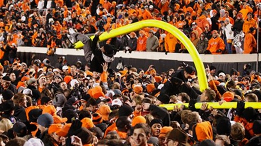 December 3, 2011: A fan hangs from a goal post after it was torn down in celebration of Oklahoma State's 44-10 win over Oklahoma in an NCAA college football game in Stillwater, Okla.