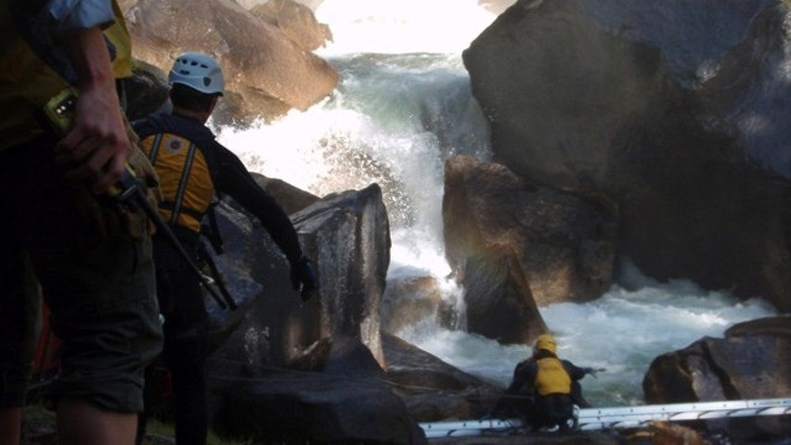 FILE - In this undated file photo provided by the National Park Service, authorities look to recover the bodies of three members of a church group who were swept into a raging waterfall at Yosemite National Park in California.