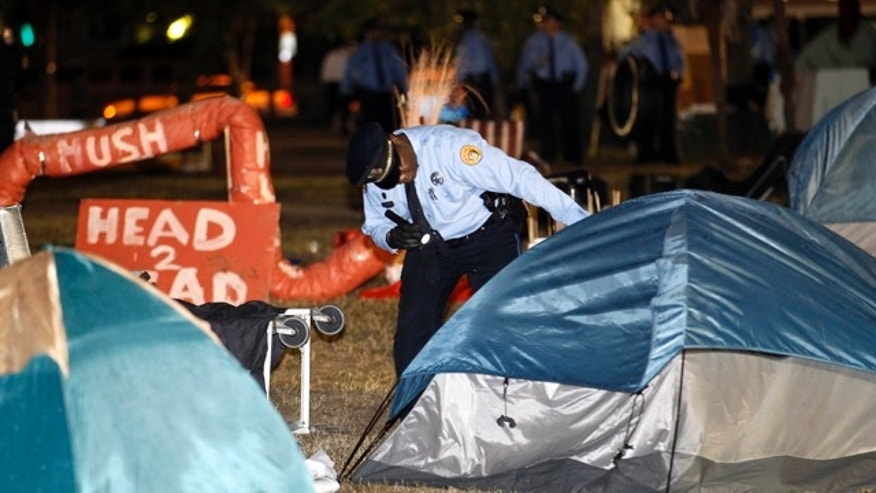 Dec. 6, 2011: A New Orleans police officer checks a tent for people as they clear out the Occupy New Orleans encampment in Duncan Plaza across from City Hall in New Orleans.