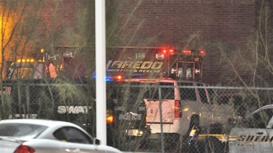 December 5, 2011: A rescue unit of the Laredo Fire Department is stationed at a side entrance to the Texas Health and Human Services Offices. A Texas woman who for months was unable to qualify for food stamps pulled a gun in a state welfare office and staged a seven-hour standoff with police that ended with her shooting her two children before killing herself, officials said Tuesday.
