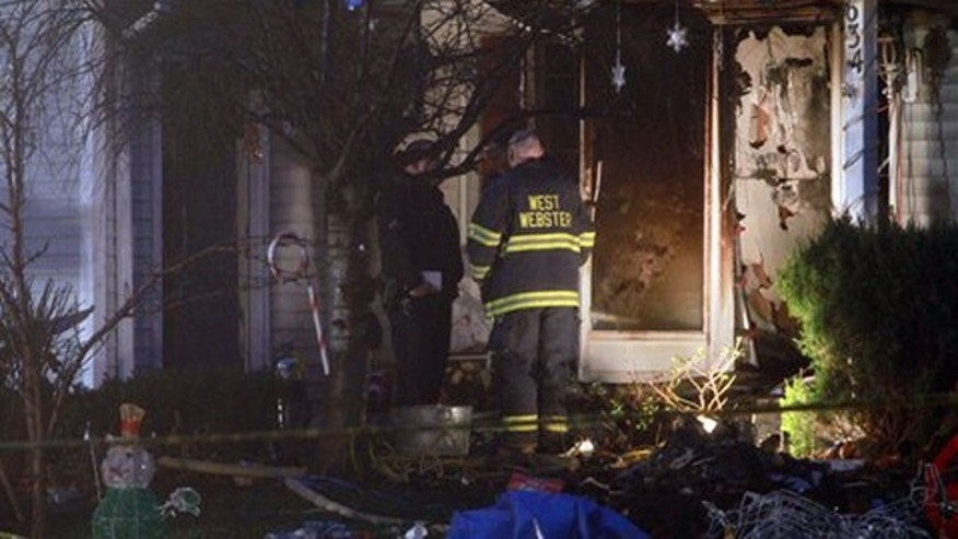 Emergency personnel investigate outside a home after a fire in Webster, NY on Wednesday, Dec.  7, 2011.