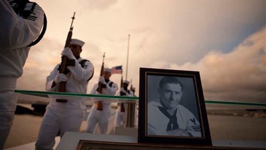 Dec. 6: Navy Region Hawaii Honor Guard march past a photograph of Pearl Harbor survivor Lee Soucy during the internment ceremony for Soucy in Honolulu. Soucy, who died last year at the age of 90, wanted to have his ashes interred inside the USS Utah, his ship that sank during the surprise Japanese attack on Pearl Harbor in Dec. 7, 1941.