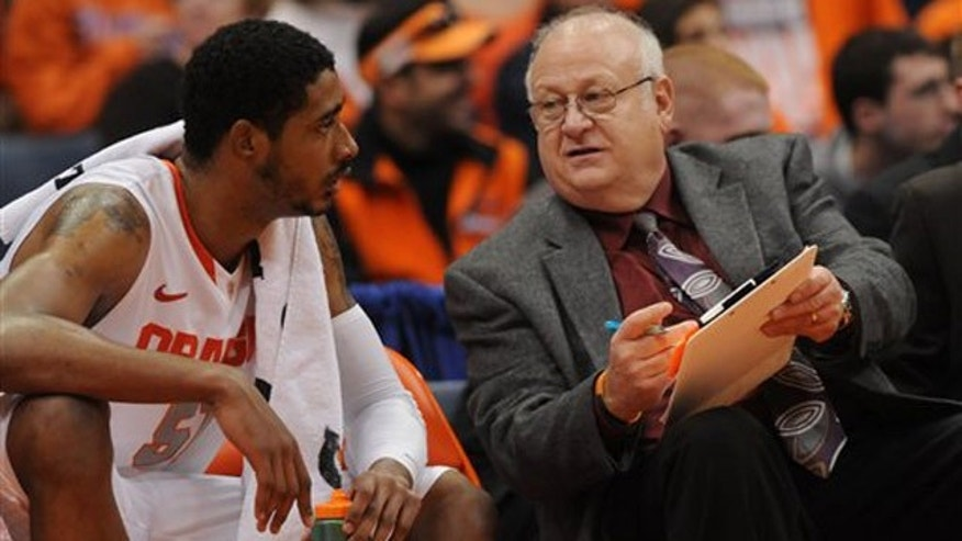 This Nov. 12, 2001 photo shows Syracuse assistant basketball coach Bernie Fine talking to Fab Melo on the bench during a game against Fordham, in Syracuse, N.Y.