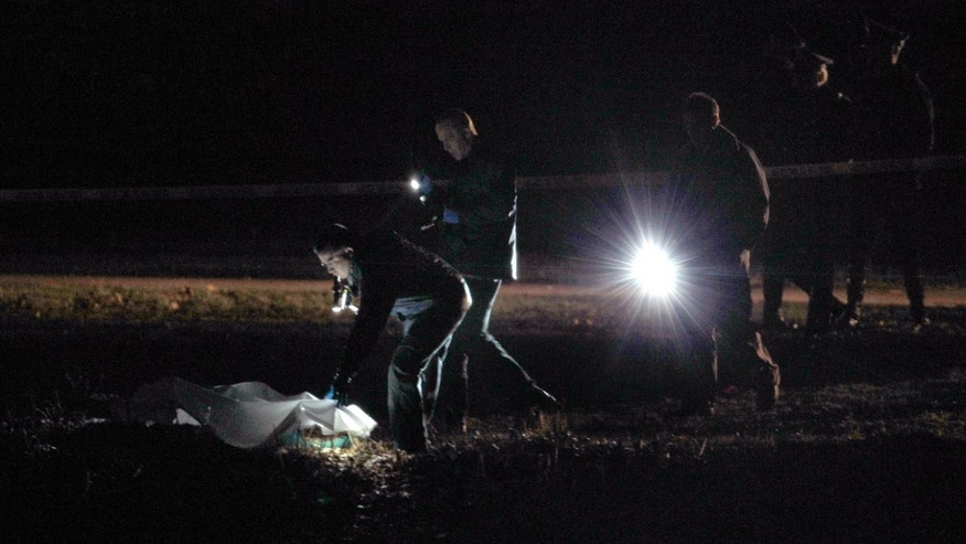 Dec. 9, 2011:nvestigators examine a crime scene along the Charles River in Boston.