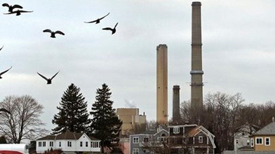 December 14, 2011: Pigeons fly past as the stacks of Dominion's power plant tower over a nearby neighborhood in Salem, Mass.