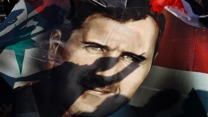 Dec. 16: Shadows of Syrians are reflected on a giant poster showing President Bashar Assad, during a supporting rally in Damascus, Syria.