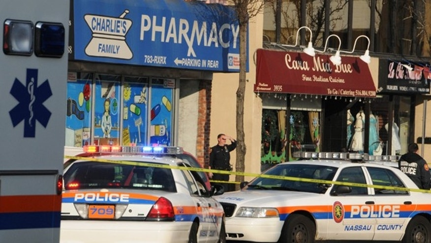 Dec. 31: A police officer stands on the sidewalk in front of Charlies Family Pharmacy in Seaford, N.Y., after a robber was killed while fleeing the store.