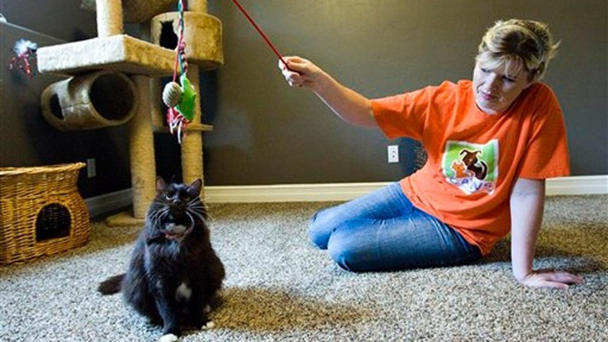 Janita Coombs plays with her cat, Andrea, at her Syracuse, Utah home.