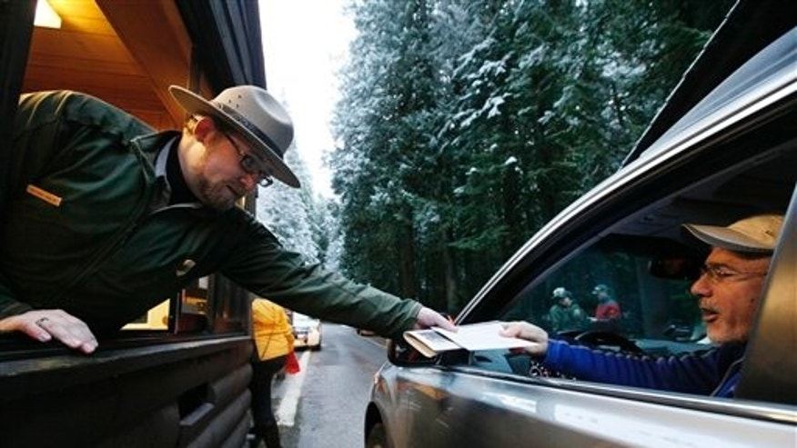 Jan. 7: Mount Rainier National Park Ranger Matt Chalup hands park information to one of the first visitors to the park at the Nisqually entrance near Ashford, Wash.