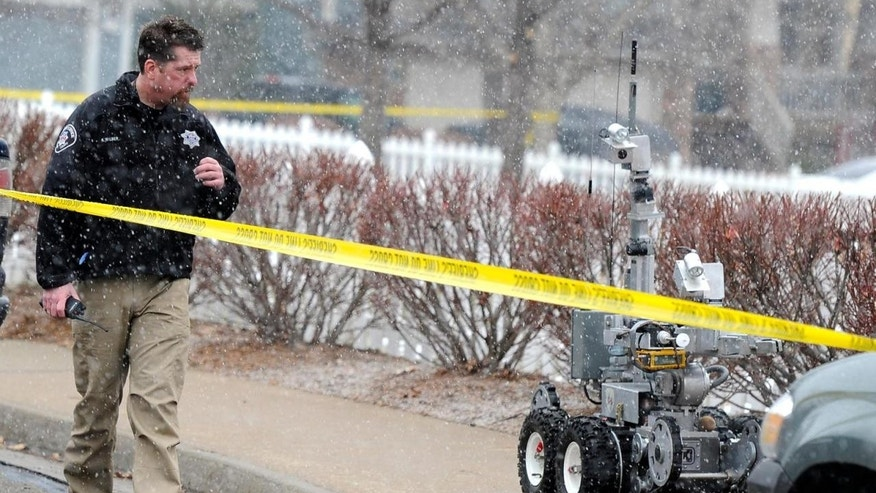 Jan. 7, 2012: A police officer walks beside a robot used in bomb situations as he responds to an explosion in a car Saturday near 337 Lodgewood Point in Lafayette, Colo.
