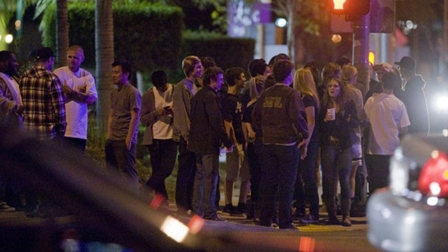 January 13, 2012: A crowd gathers at the intersection of Imperial Highway and La Palma in Anaheim, Calif. Friday night following the discovery of a dead man behind a Carl's Jr.