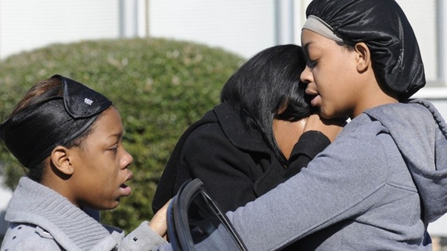 Jan. 29, 2012: Ravenn Carlton, center, wife of one of the five people found dead is comforted by Nakia Carlton, left, and Khalena Carlton, right, near the scene where five people were found dead inside a house in Birmingham, Ala.