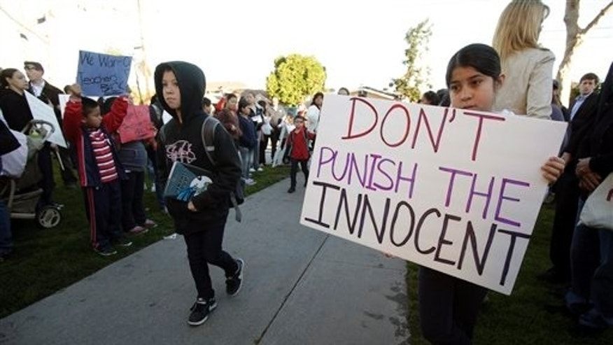 Feb. 9: Nine-year-old Ruby Garduno, right, holds a sign as students enter Miramonte Elementary School in Los Angeles.