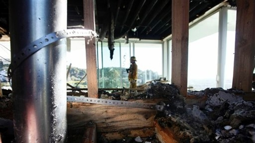 Feb. 17, 2011: A Los Angeles Fire Department arson investigator stands amid the charred ruins of a Hollywood Hills mansion where a ceiling collapsed on firefighter Glen Allen and five other firefighters during the Feb. 16 fire.