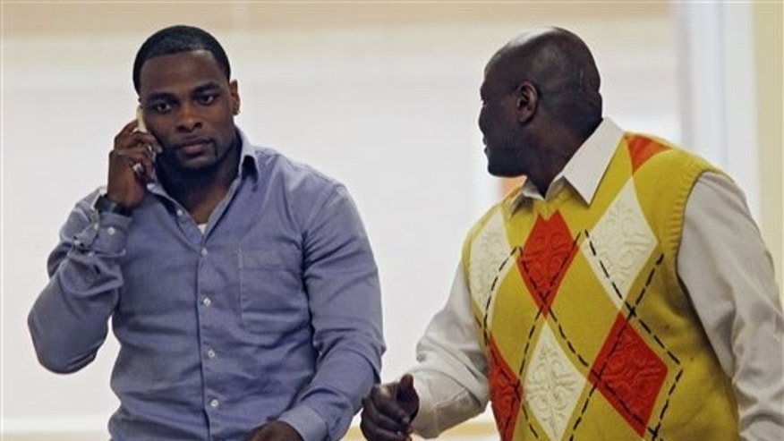 March 1: Former Denver Broncos cornerback Perrish Cox, left,  talks on his phone as he walks the hallway with his uncle, Ron Davis, outside the courtroom in Castle Rock, Colorado.