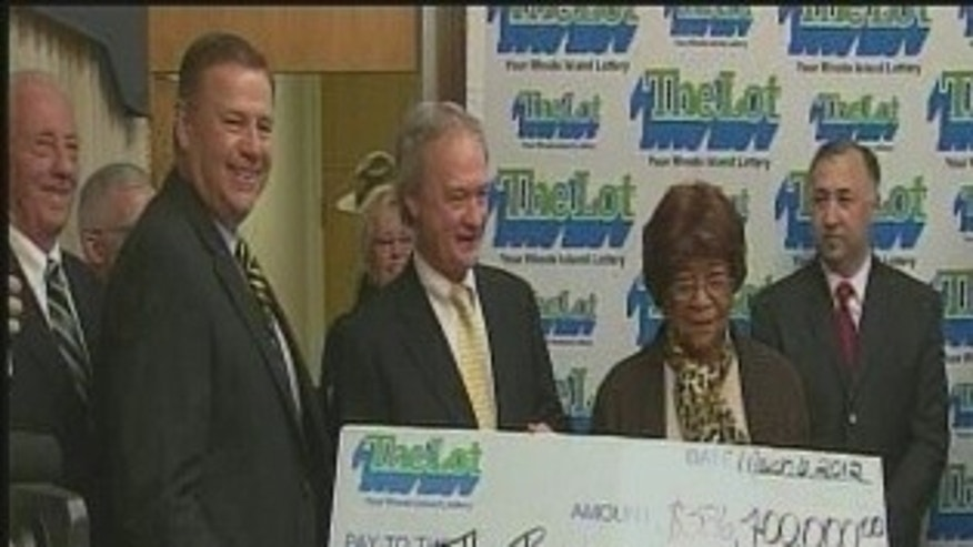 Rhode Island Lottery Director Gerald Aubin and Gov. Lincoln Chafee present White with the $336.4 million check (WPRI/WNAC).