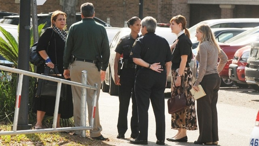 March 6, 2012: State attorney Angela Corey, left, speaks with investigators and faculty near the back entrance of Episcopal High School in Jacksonville, Fla. after a shooting at the school.
