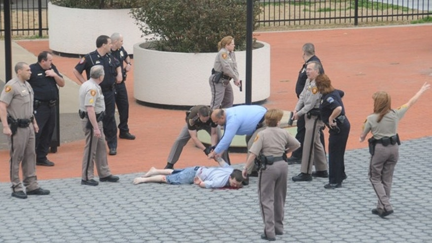 March 7: In this photo provided by John Fancher of the Tulsa City-County Library, sheriff's deputies and other law enforcement officers handcuff a man who was wounded in an exchange of gunfire with law enforcement officers on the plaza in between the library and the Tulsa County Courthouse in Tulsa, Okla.