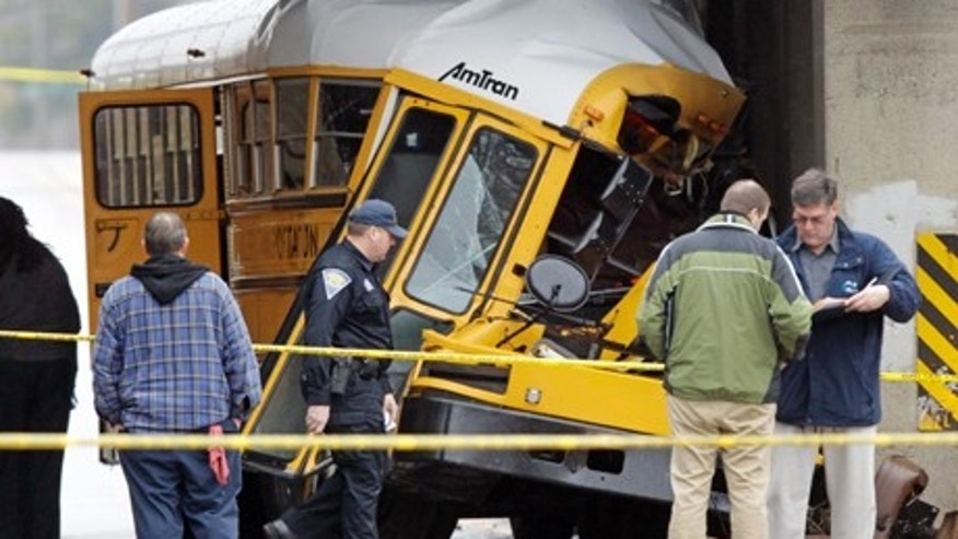 March 12, 2012- Investigators work the scene of a fatal bus crash on the southeast side of Indianapolis. The driver and one student were killed and two others critically injured.  (AP Photo/Michael Conroy)