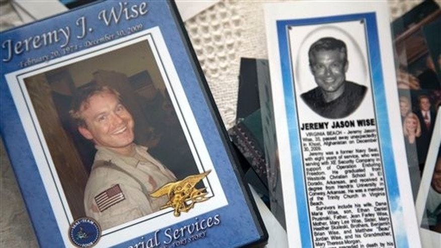 In this photo, taken Jan. 24, 2012, the image of former Navy Seal Jeremy Wise is shown on the cover of a video of his 2009 memorial service and a newspaper obit displayed at his sister's home in Prescott, Ark.