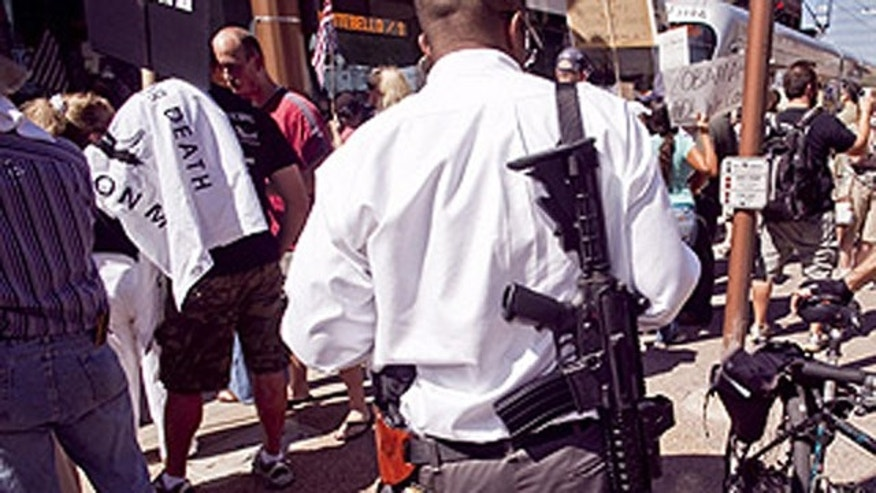 Aug. 17: A man carries a military style AR-15 rifle during an Obama opposition rally in Phoenix.