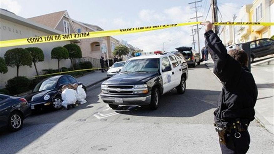 March 23, 2012: San Francisco Police officers inspect outside of a home on Howth Street in San Francisco.