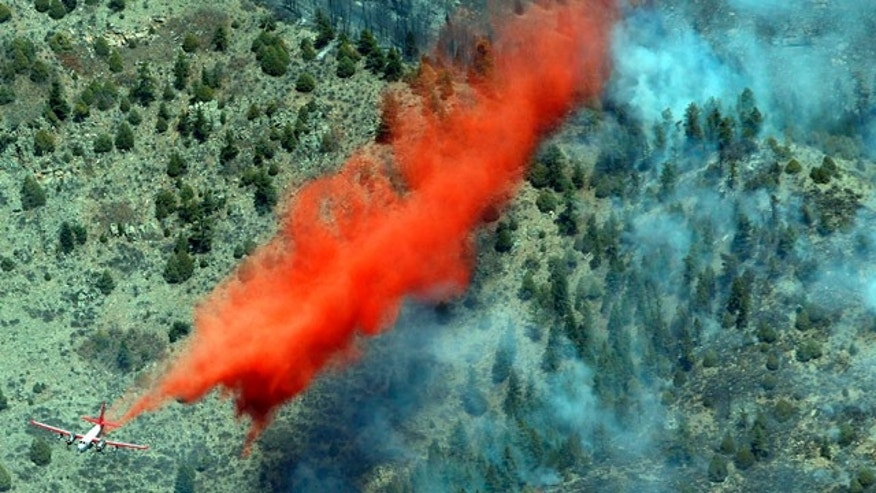 March 27: A trail of slurry is deposited by a bomber during a run over a smoldering ridge in the Lower North Fork Wildfire burning in the foothills community of Conifer, Colo.
