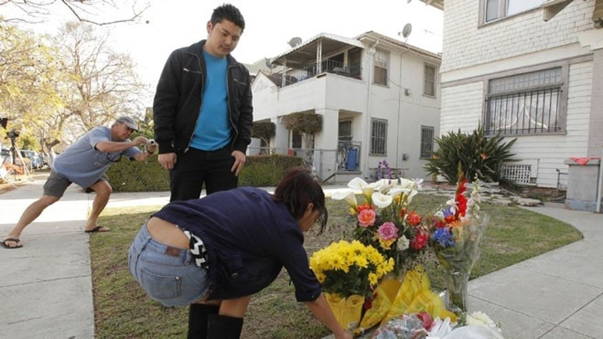 April 11, 2012: Neighbors Araceli Van Dine, right, and Derek Van Dine, middle, bring flowers to the site of the slayings of two USC graduate students early Wednesday in Los Angeles.