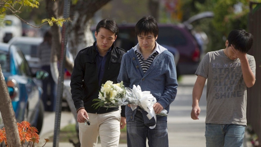 April 11: University of Southern California students bring flowers to the site of the slayings of their friends in Los Angeles.