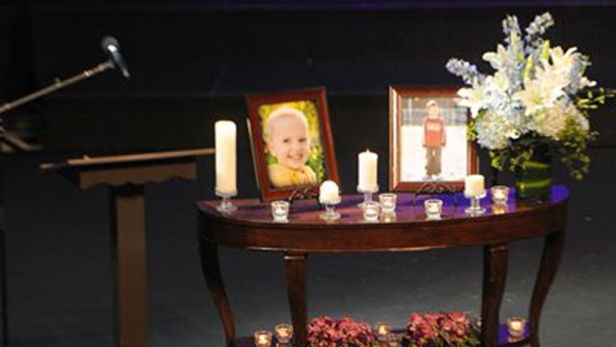 Feb. 11, 2012: Photos of Charlie, right, and Braden Powell are displayed next to the casket they shared during their funeral service.